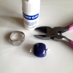 Add a little dot of glue to each knot to secure them. Then glue bead to ring setting.