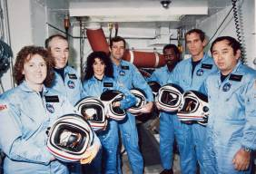 In this photo from Jan. 9, 1986, the Challenger crew takes a break during countdown training at NASA's Kennedy Space Center. Left to right are Teacher-in-Space payload specialist Sharon Christa McAuliffe; payload specialist Gregory Jarvis; and astronauts Judith A. Resnik, mission specialist; Francis R. (Dick) Scobee, mission commander; Ronald E. McNair, mission specialist; Mike J. Smith, pilot; and Ellison S. Onizuka, mission specialist.