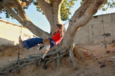 A Palestinian girl plays on a makeshift swing in Khan Younis in the southern Gaza Strip