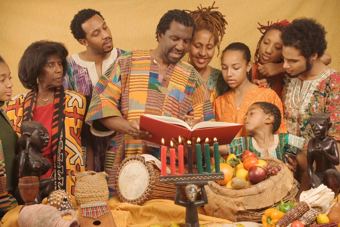 Family lighting candles celebrating Kwanzaa --- Image by © Royalty-Free/Corbis