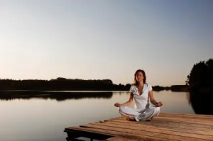Mujer meditando lago
