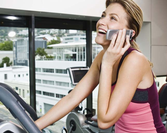 Smiling woman with cell phone on exercise bike at gym