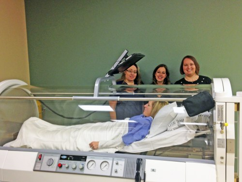 Stacy Martin, Jessica Midlow, and Melissa Vodicka demonstrate how to use the new hyperbaric oxygen chamber with Victoria Stone.