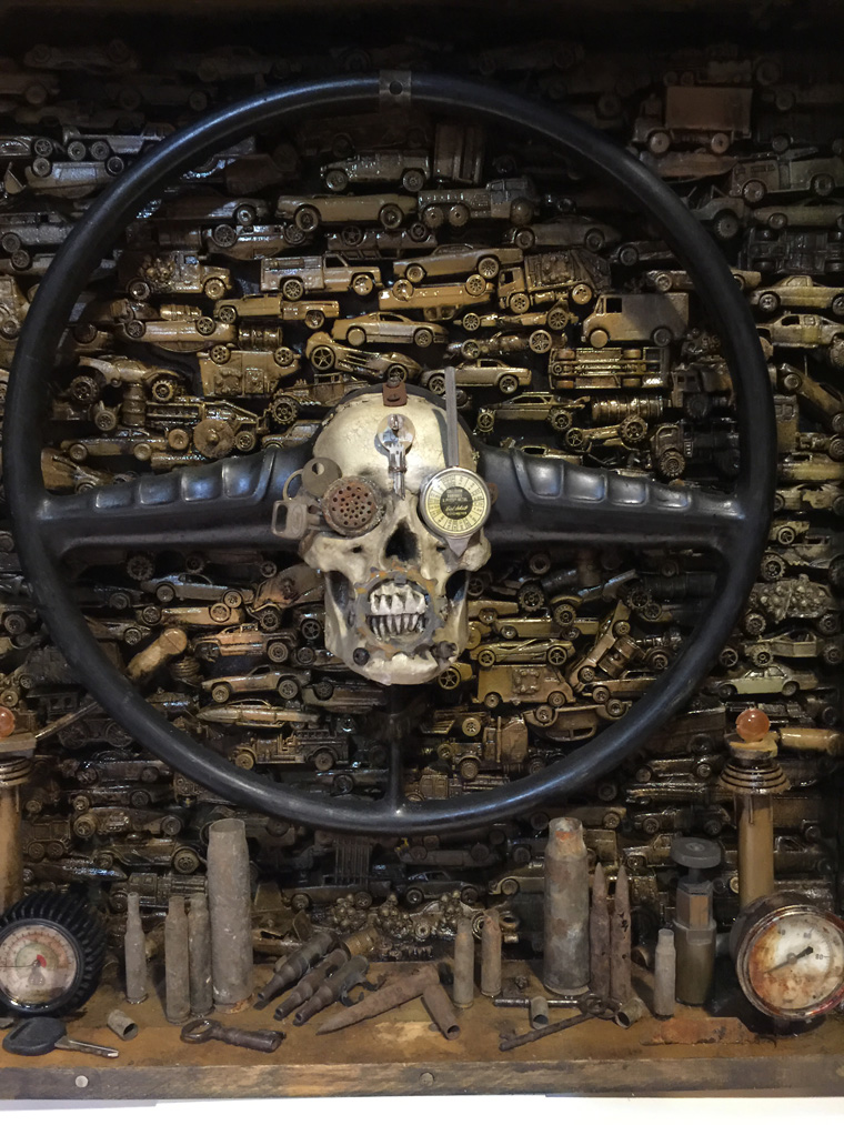 "Krystopher Sapp - I Shall Ride Eternal Based on ""Mad Max Fury Road"" 1956 steering wheels and various car parts, 150 Hot Wheel cars, resin castings, with custom built metal frame from machine parts and military gun parts, 25.5x24x7"" $2,500"