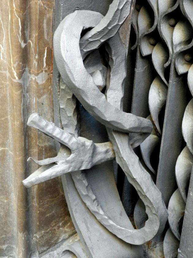 Detalle de una serpiente en la puerta de entrada al Palau