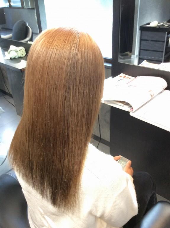 金髪までブリーチした白髪の女性の後ろ姿のヘアー写真です。斜め後ろから写真を撮りました。美容室のライトを反射してピッカピカ状態です。縮毛矯正施術後のアフター画像です。毛先部分は真っ直ぐに伸びています。美しい髪の毛です。