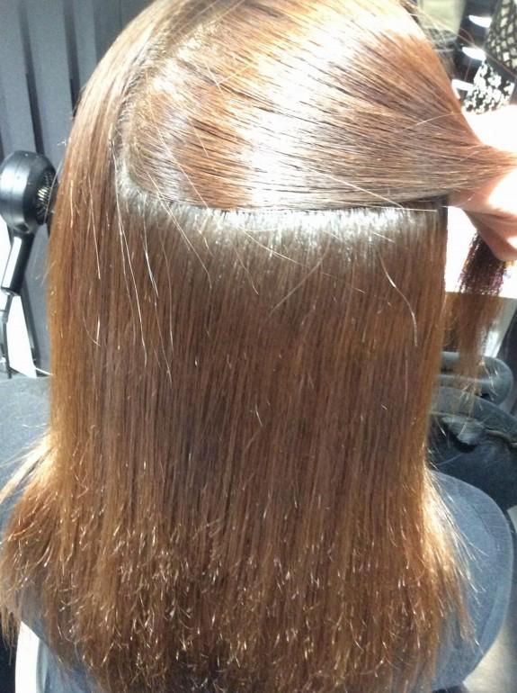 縮毛矯正施術後のアフター画像です。表面の髪の毛を取り持ち上げて中の状態が良く見えるようにしています。毛先以外はピカピカとライトをうまく反射していますのでとても綺麗です。ツヤが出て大変綺麗な髪の毛です。こんなに美しい髪の毛はそうそう見れるものでは有りません。