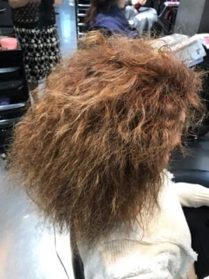 陰毛の様な感じのくせ毛です。ブリーチを自分でしているのでムラだらけです。そんな女性を美容室の鏡の前に座ってもらい右側真横から写真に撮った。髪の毛は爆発している状態です。昔のカーリーヘアーの様な感じです。ボンバーヘアーとでも言いましょうか。黒人のくせ毛に近いです。