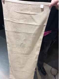 モカ色のタオルを広げて画面一杯に写真を撮りました。後ろで人が指でつまんで持っていますので、人差し指、中指、親指がみえます。後ろのひとのブーツも写っています。