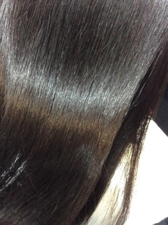 画面一杯に髪の毛がウェーブしている状態で写っています。真ん中辺りに光が反射して美しい髪の毛と認識できる。髪の毛一本一本ツルツル状態で直毛を感じさせる。髪の毛は黒髪でしなやかでシットリとした感じです。柔らかい感触が伝わってきます。