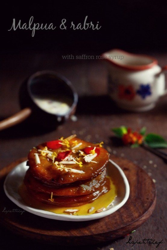 Malpua with rabri, a festive delicacy with the power to make anyone happy. Flavored with cardamom,fennel and jaggery,stuffed with mawa and raisins these sweet pancakes are like delicious bites of heaven. Served with an exotic rose and saffron syrup and thick clotted cream(rabri) these malpuas are  soft and melting in the centre with crisp laced edges.
