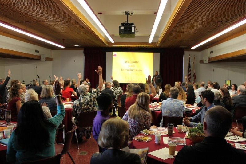 Guests at the State of the College meeting raise their hands in response to Tod A. Burnett asking how many of them attended Saddleback College as students. (Saddleback College President's Gaucho Gazette)