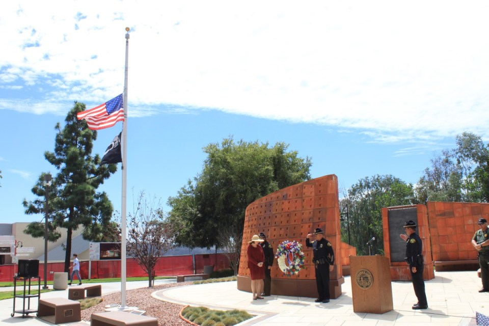 Police officers and other stand in tribute next to the Veterans Memorial to honor the heroes from September 11, 2001. (Saddleback Public Information and Marketing Office)