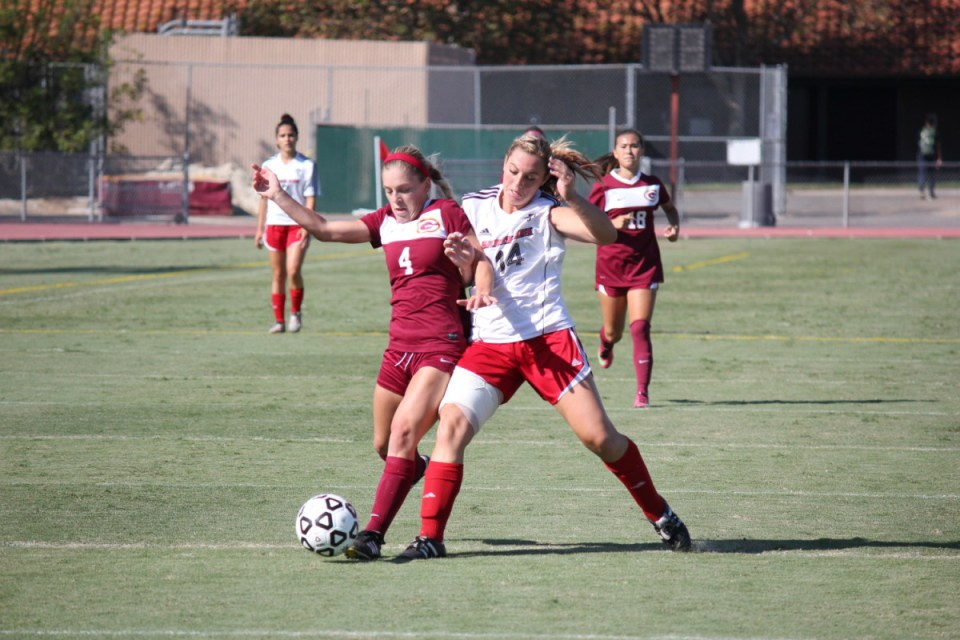 Gauchos freshman forward Emilee Monnig (No. 4, red) gets the ball up over the defense in action. (Dominic Ebel/Lariat)