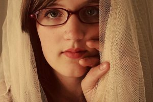 Lady stares while hiding behind a curtain. New study places sexual assaults at one in four women. (Wiki Commons)