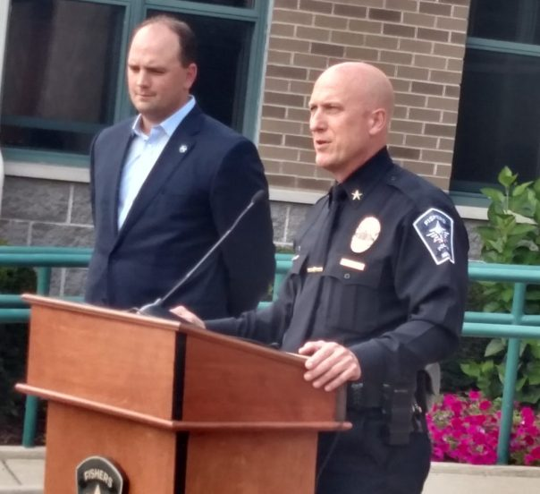 Chief Mitch Thompson speaks to the crowd after being sworn-in, as Mayor Scott Fadness looks on
