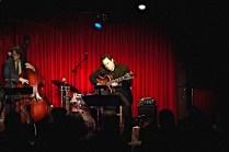photo of Larry Koonse seated playing guitar spotlit onstage with Sara Gazarek Band