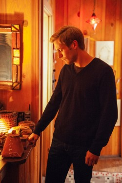 Theo Green (Zachary Booth) looking at family mementos in LAST WEEKEND.