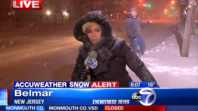 Guy Shreds on His Air Guitar Behind TV News Reporter During a Snowy Weather Alert