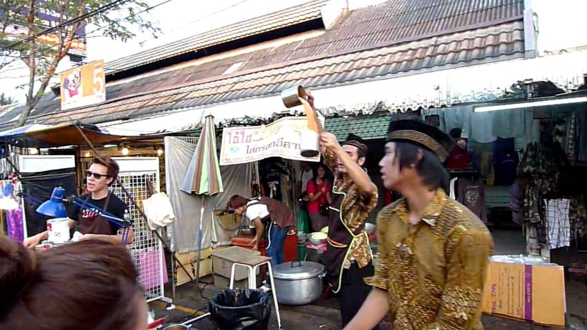 A Man in an Outdoor Market Appears to Bend the Laws of Physics While Pouring Tea Between Two Pitchers