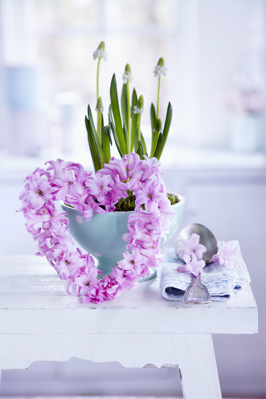 Small, heart-shaped wreaths of hyacinth florets in front of bowl of grape hyacinths