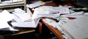 Picture of desk piled with papers.