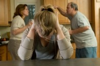 Image of parents arguing and daughter covering her ears.