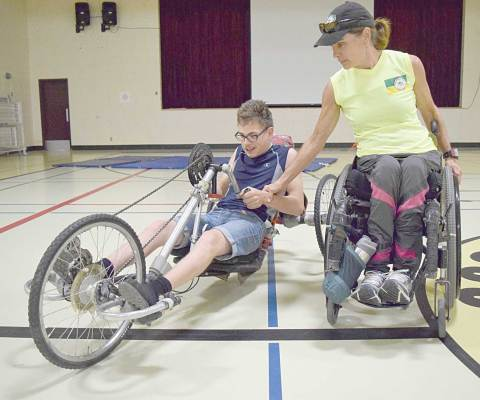 Craik student Quinn Nielson takes a spin in a handcycle under the guidance of former Paralympic athlete Colette Bourgonje.