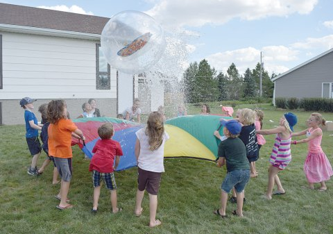Children play an outdoor game involving a giant parachute, a large ball and lots of water at Vacation Bible School in Davidson on Tuesday.