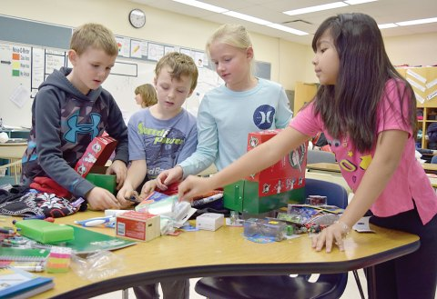 From left, Grade 3 students Mason Berry, Sam Kinder, Emry Palmer and Ella Saclao pick items for their boxes on Wednesday for the Operation Christmas Child program at Davidson School.