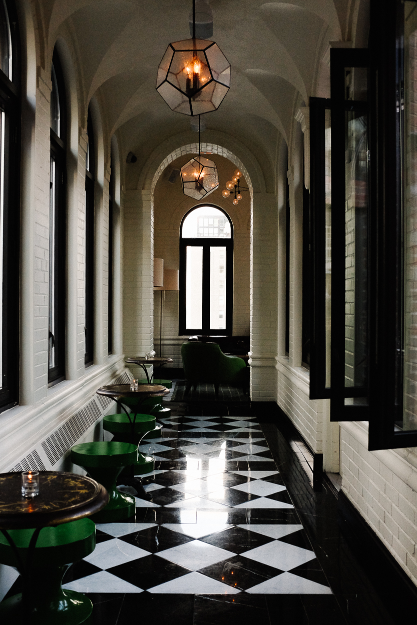 Checkerboard tile hallways lined with french windows on either side anchor the hotel's feel.