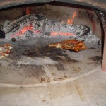 """After the fire has burned for 30-40mins, spread the coals around the back of the oven. Then, brush the base, and spread corn meal or flower for the pizza to cook on."""