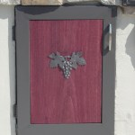 Custom steel doors with Purple Heart wood panels and iron deco grapes.