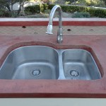 """24"""" stainless steel sink reset into the concrete counter tops."""