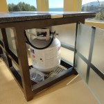 Features glass access door for propane tank storage.