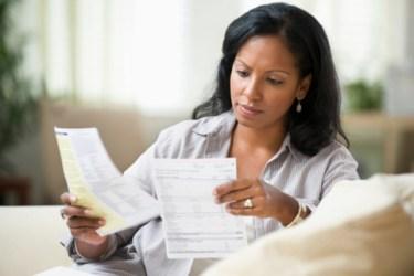 Hispanic woman sitting on sofa reading bills