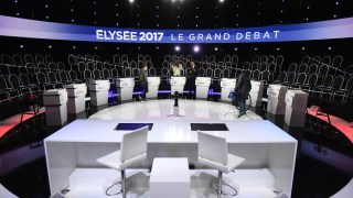 Staff members prepare the TV set before the debate organised by French private TV channels BFM TV and CNews, between the eleven candidates for the French presidential election, on April 4, 2017 in La Plaine-Saint-Denis. / AFP PHOTO / POOL / Lionel BONAVENTURE