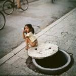 Jeune fille assise auprès d'un abri anti aérien