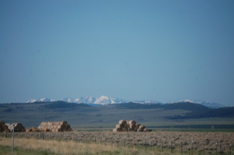 Battling peaks of hay challenge the snow capped peaks in the distance south of White Sulphur Springs