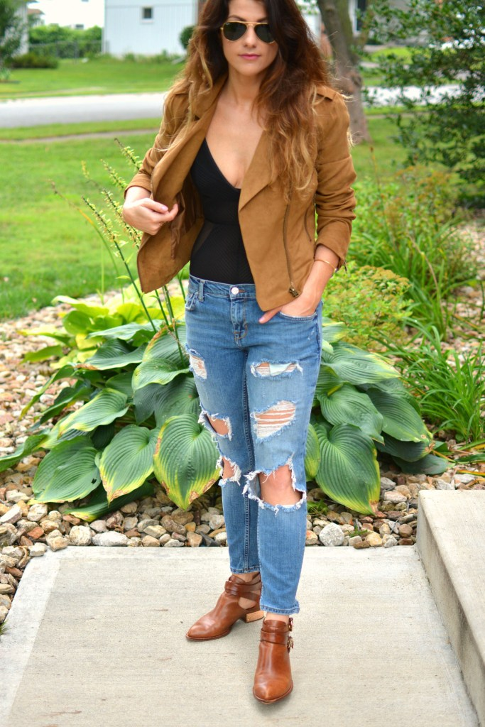 ashley from lsr in a faux suede jacket, ripped jeans, sheer bodysuit, and ankle booties
