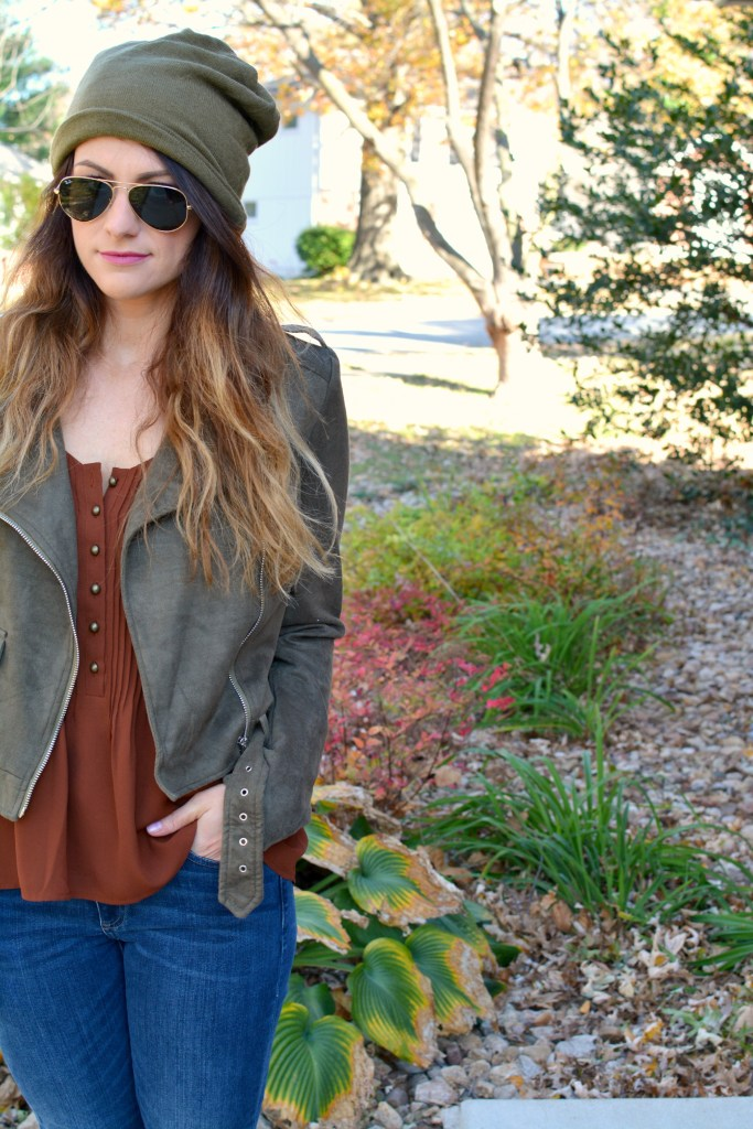 Ashley from LSR in an olive green beanie, olive green suede motorcycle jacket, and an Express tank.