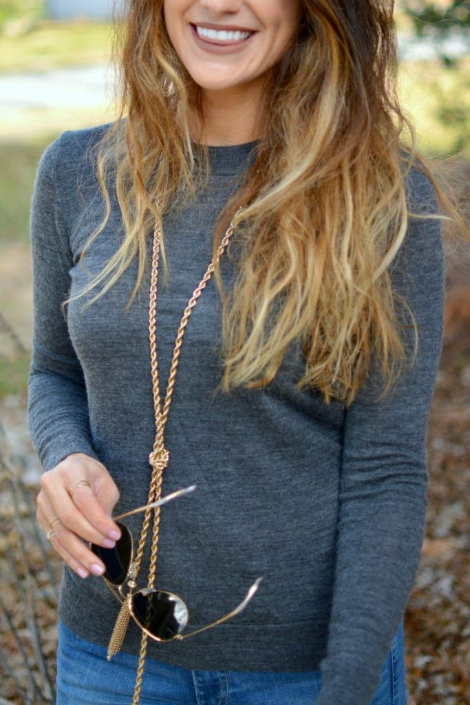 Ashley from LSR in a gray sweater and BaubleBar lariat necklace