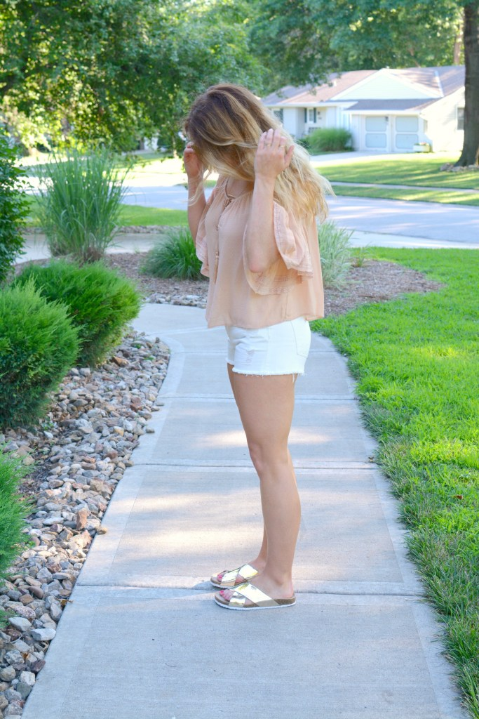 Ashley from LSR in a blush top from Zara, white denim shorts, and metallic slides