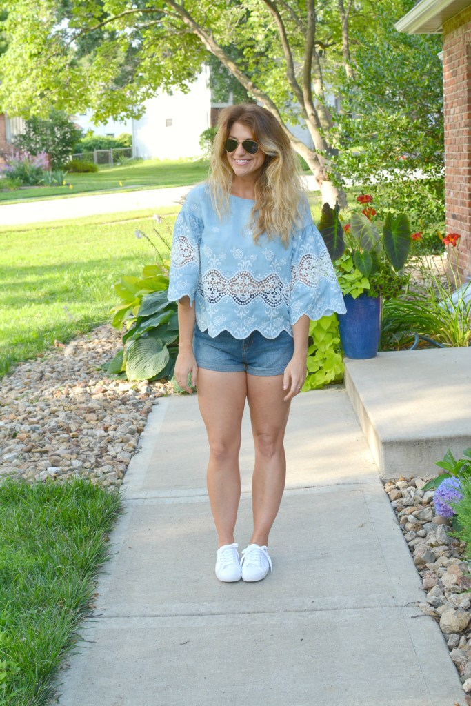 Ashley from LSR in a chambray and lace blouse, denim shorts, and white sneakers