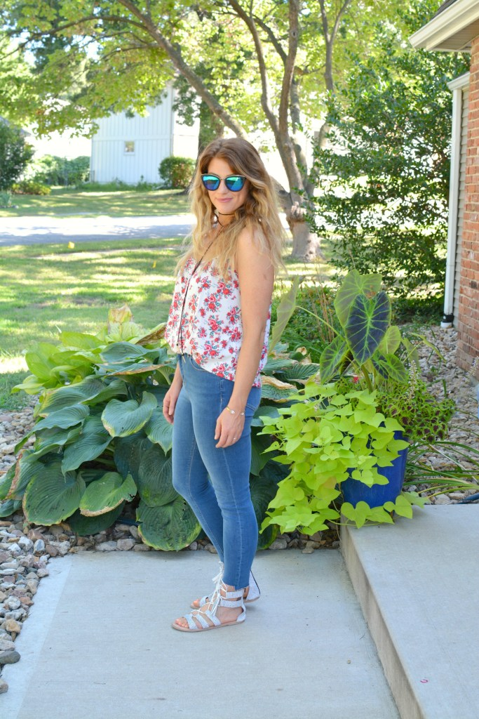 Ashley from LSR in a floral tank, stepped hem jeans, and white lace-up sandals