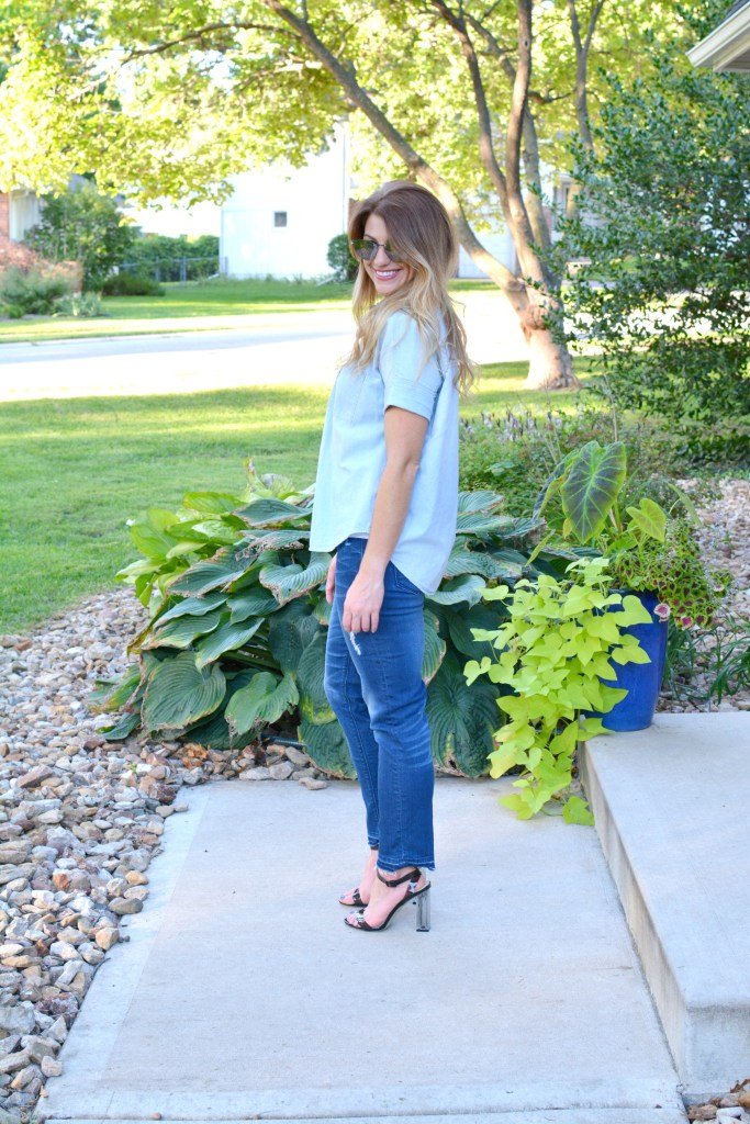 Ashley from LSR in a light chambray shirt, raw hem jeans, and lucite heels