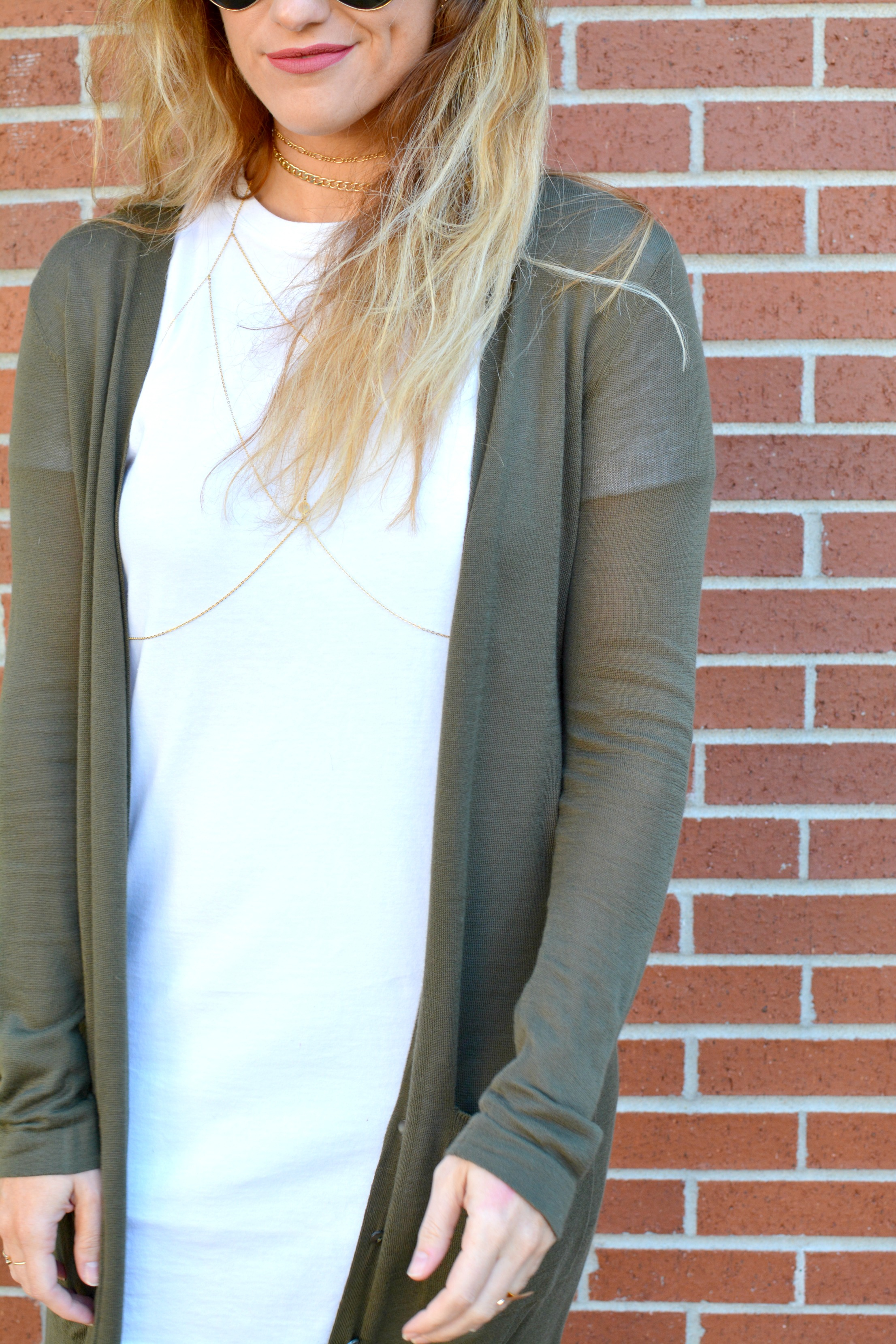 Ashley from LSR in an olive long cardigan, t-shirt dress, body chain, and chain chokers