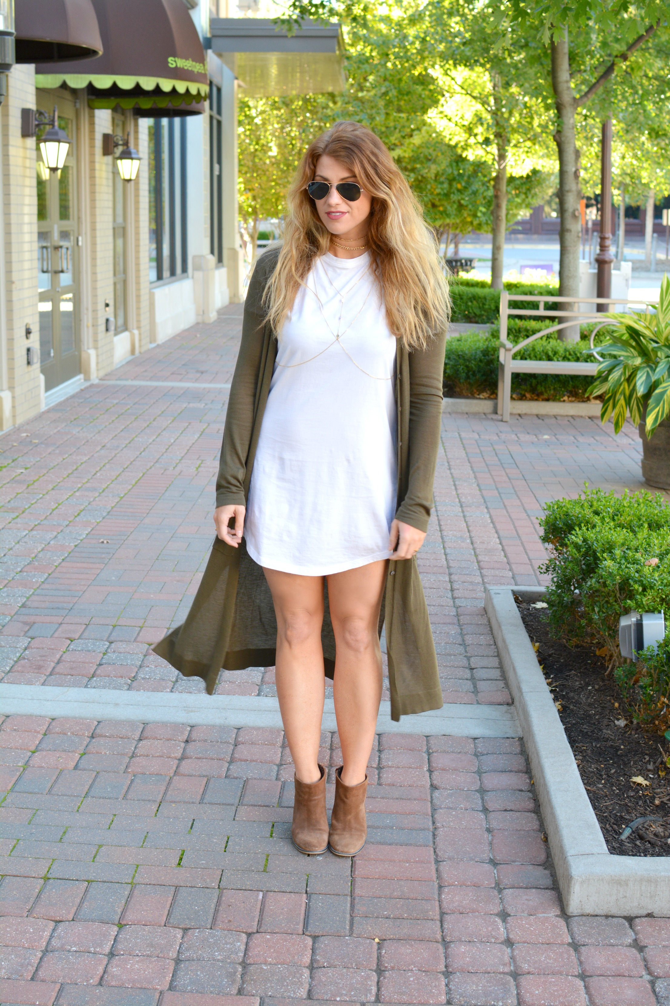 Ashley from LSR in an olive long cardigan, t-shirt dress, and suede ankle boots