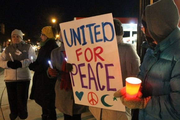 PHOTOS: Candlelight Vigil For World Peace Greets Commuters