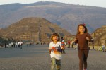 Alex and Nadia running towards the Pyramid of the Feathered Serpent on the Avenue of the Dead in Teotihuacan, Mexico. In the background, the Pyramid of the Moon.